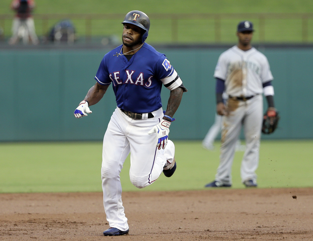 Texas Rangers' Delino DeShields rounds the bases after hitting a leadoff solo home run, as Seattle Mariners shortstop Jean Segura, rear, watches durin...