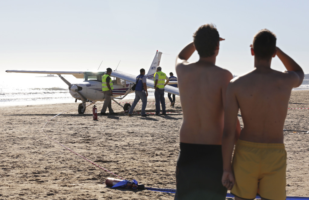 Two men look at a small plane after an emergency landing on Sao Joao beach in Costa da Caparica, outside Lisbon, Wednesday, Aug. 2, 2017. The light pl...
