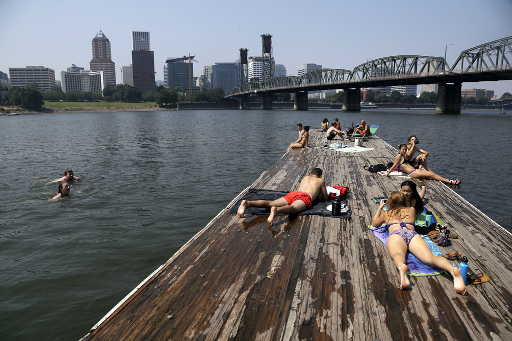 People sunbathe and cool off in the Willamette River with the downtown skyline visible in the background in Portland, Ore., Wednesday, Aug. 2, 2017. S...