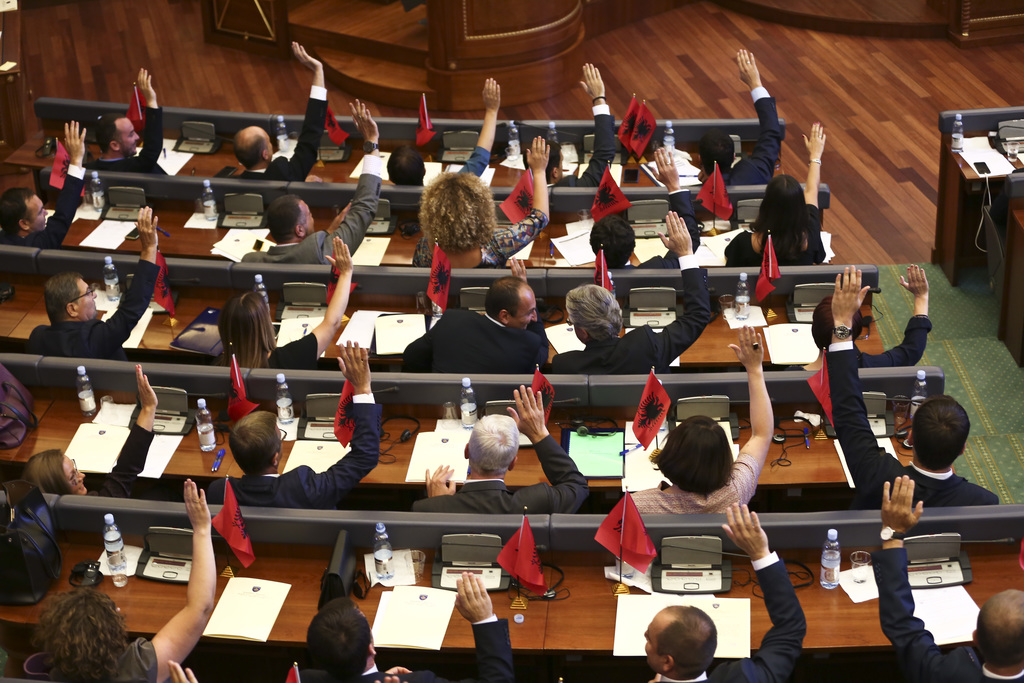 Kosovo opposition lawmakers vote during a parliamentary session, in Pristina, Thursday, Aug. 3, 2017. Kosovo's 120 new lawmakers have been sworn in du...