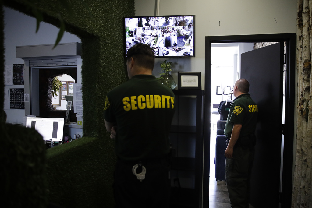 In this June 27, 2017, photo, two security guard workers at the Higher Path medical marijuana dispensary owned by Jerred Kiloh in Los Angeles. Kiloh's...