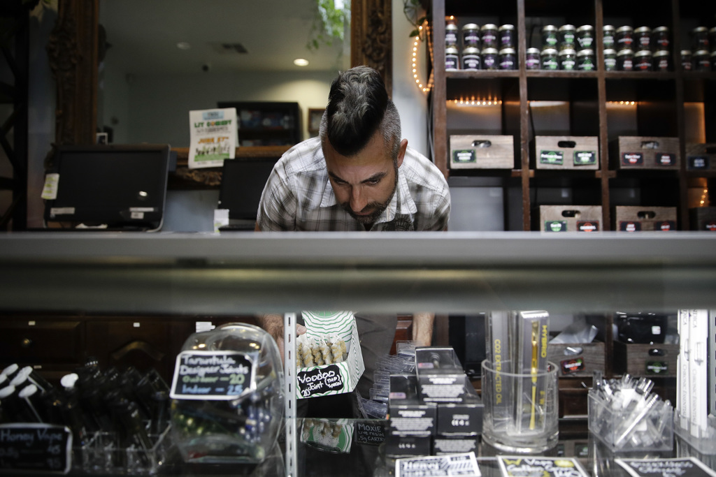 In this June 27, 2017, photo, Jerred Kiloh, owner of the Higher Path medical marijuana dispensary, stocks shelves with with cannabis products in Los A...