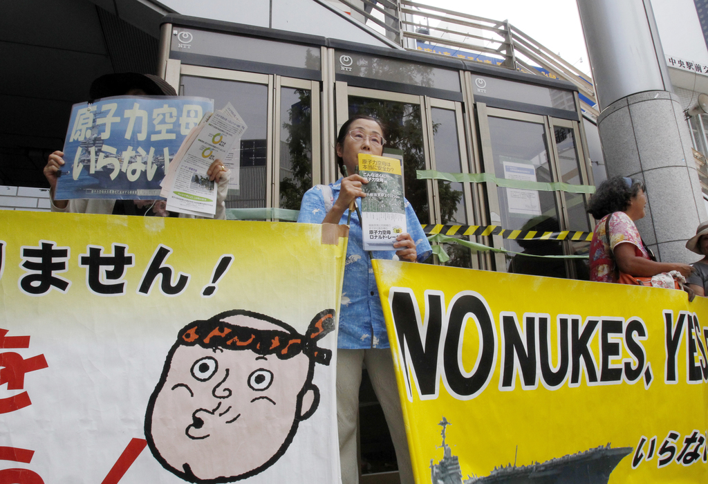 In this Tuesday, Aug. 1, 2017, photo, members of an anti-nuclear pacifist citizens' group protest outside Yokosuka-chuo Station in Yokosuka, south of ...