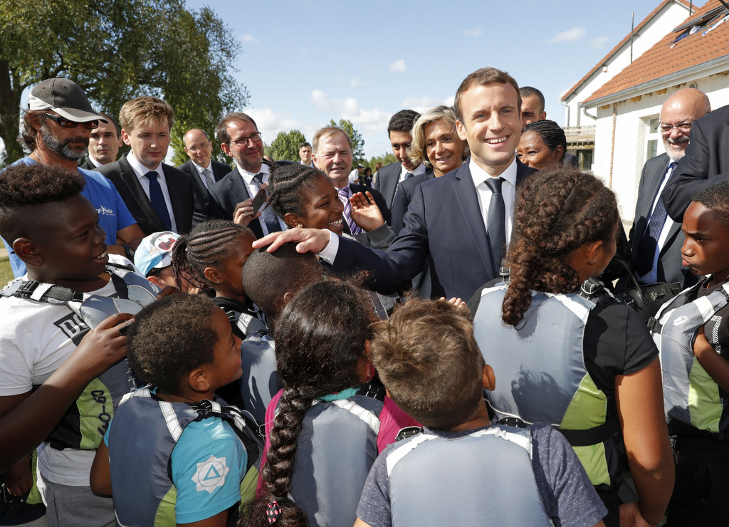 French President Emmanuel Macron greets children as he visits a recreation center in Moisson, east of Paris, France, Thursday, Aug. 3, 2017. French Pr...