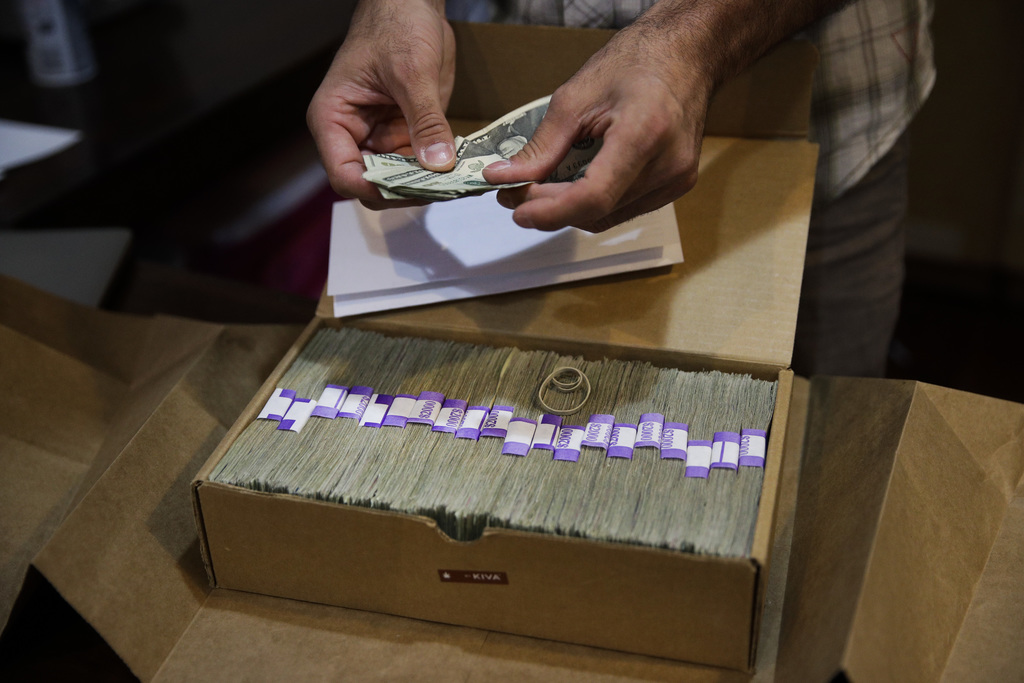 In this June 27, 2017, photo, Jerred Kiloh, owner of the Higher Path medical marijuana dispensary, prepares his monthly tax payment, $40,131.88 in cas...