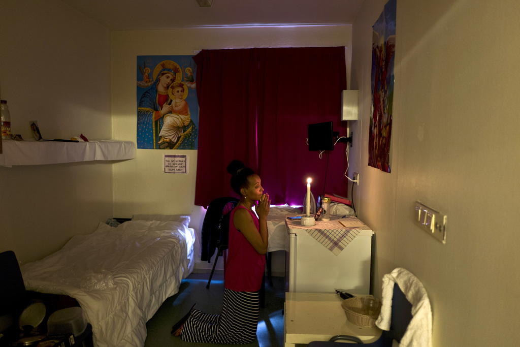 In this Monday, June 26, 2017 photo, Meza Negadtu, 29, a migrant from Eritrea, prays inside her room at the former prison of Bijlmerbajes, in Amsterda...