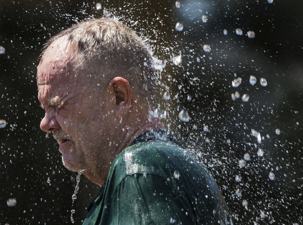 Robert Nelson, 59, soaks in the EWEB fountain along the banks of the Willamette River in Eugene, Ore., Wednesday, Aug. 2, 2017, as temperatures climb ...