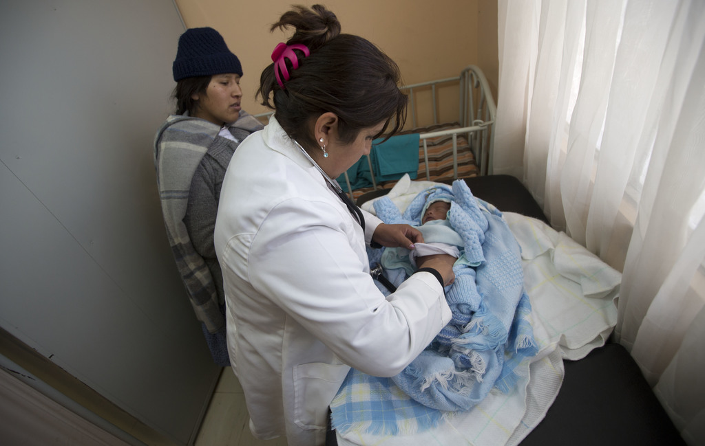 In this June 27, 2017 photo, Dr. Milenkha Chavez gives a routine check-up to 21-day-old Abraham Dilan, who was delivered at home by a midwife, as his ...