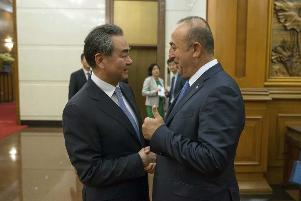 Chinese Foreign Minister Wang Yi, left, shakes hands with Turkish Foreign Minister Mevlut Cavusoglu during their meeting at Diaoyutai State Guesthouse...
