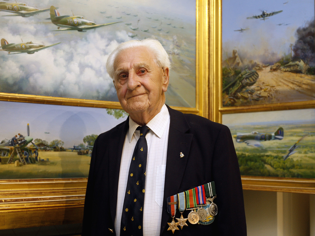 FILE - In this Thursday, Aug. 19, 2010 file photo, Ken Wilkinson an RAF veteran poses by paintings of spitfires, in London. Wilkinson, one of the last...