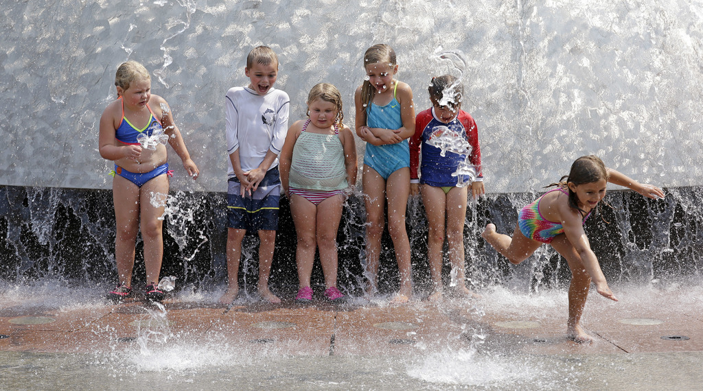 One child bolts as others hold their ground as water begins to spray out at the International Fountain at the Seattle Center during a heat wave Wednes...