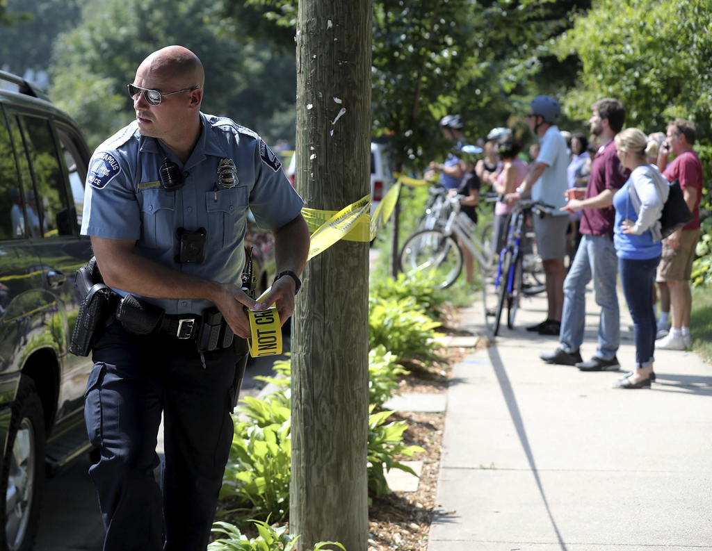 A Minneapolis police officer puts up police tape following an explosion at Minnehaha Academy Wednesday, Aug. 2, 2017, in Minneapolis. Several people a...