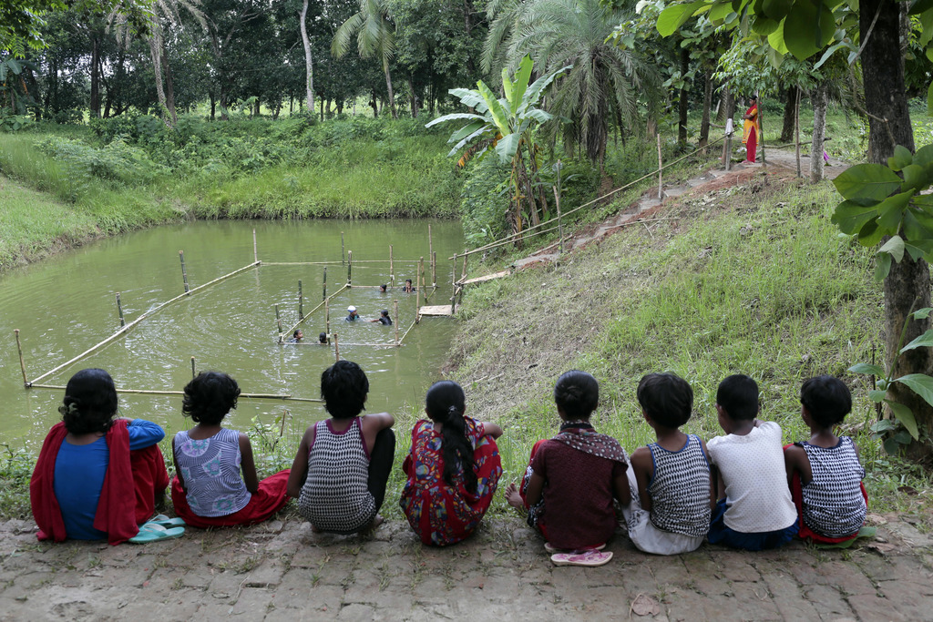 In this July 14, 2017 photo, Bangladeshi children attend a swimming training session, as others watch at a pond in the Shishu Polli Plus area in Sreep...