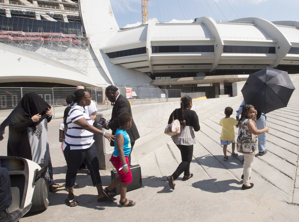 A group of asylum seekers leave Olympic Stadium to go for a walk, in Montreal on Wednesday, Aug. 2, 2017. The stadium is being used as temporary housi...