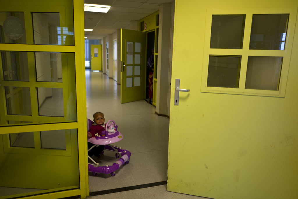 In this Tuesday, June 27, 2017 photo, Mariam Traore, an 8-month-year-old migrant from Ivory Coast, moves on a chair near her mother's room at the form...