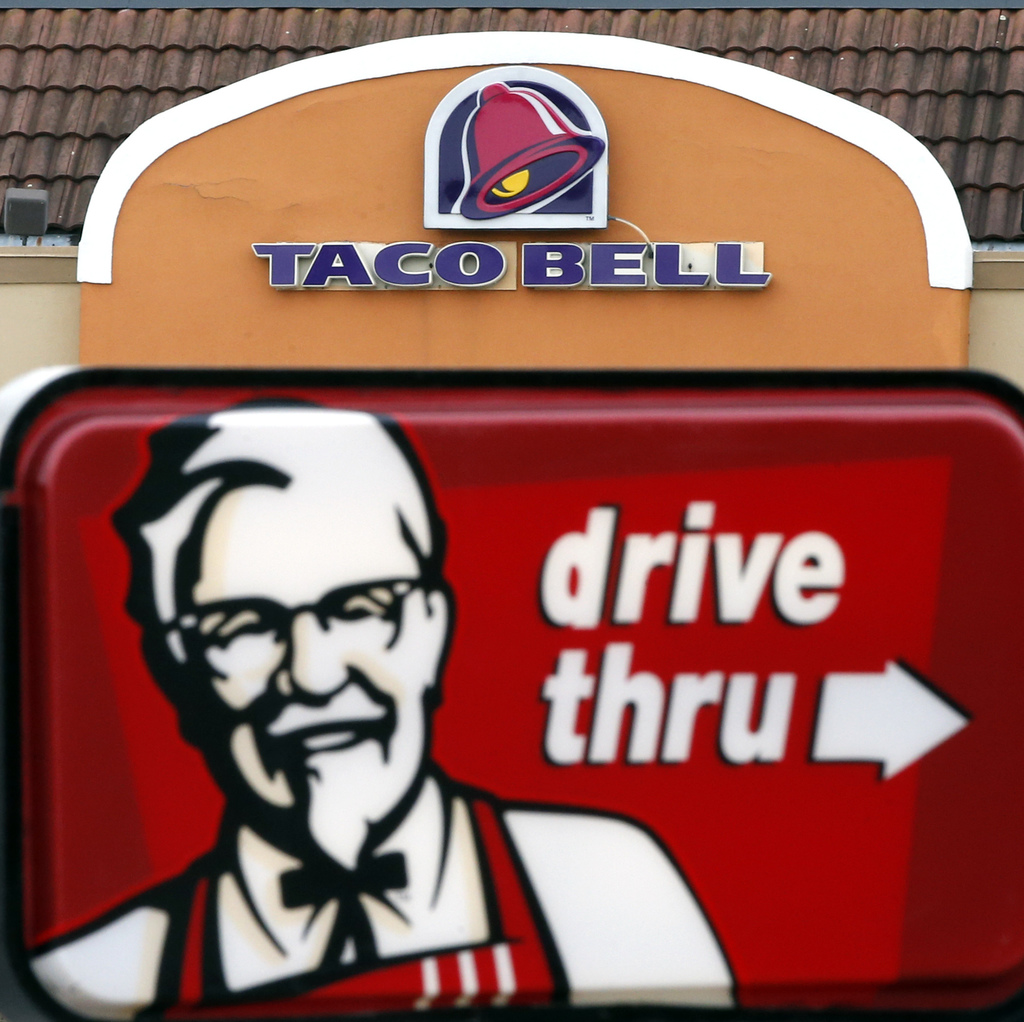 FILE - This Jan. 31, 2014, file photo, shows a Taco Bell facade behind a KFC drive-thru sign in Saugus, Mass. Yum Brands, Inc., which operates Taco Be...