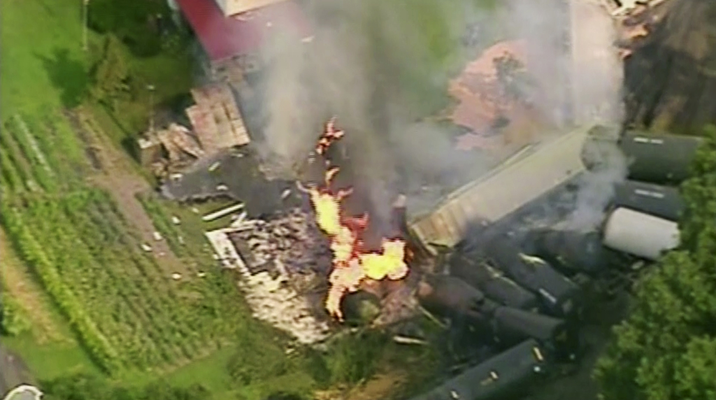 In this aerial image made from a video provided by WPXI, a fire burns after dozens of cars of a freight train carrying hazardous materials derailed in...