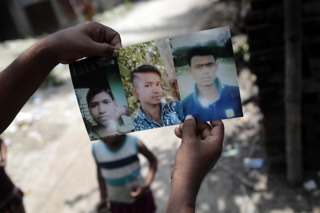 In this July 28, 2017 photo, Bangladeshi man Monir Hossain shows photographs of his sons Iqbal Hossain, 14, left, Ibrahim, 21, center, and nephew Rido...