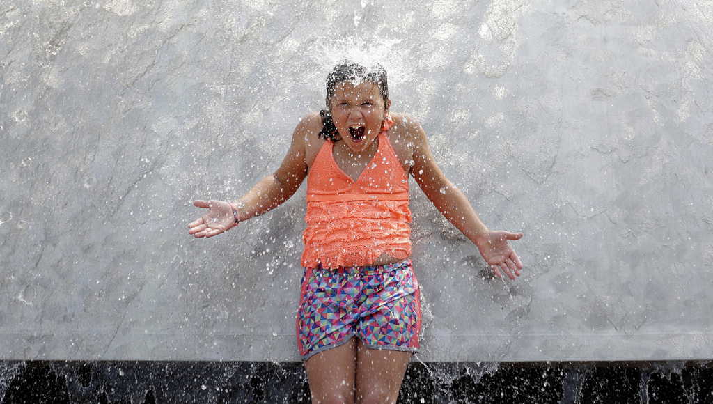 A child reacts to water pouring over her as she stands in the International Fountain at the Seattle Center during a heat wave Wednesday, Aug. 2, 2017,...