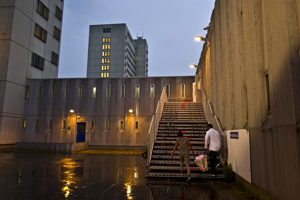 In this Thursday, July 6, 2017 photo, migrants carry a bag while walking back to their room at the former prison of Bijlmerbajes in Amsterdam, Netherl...