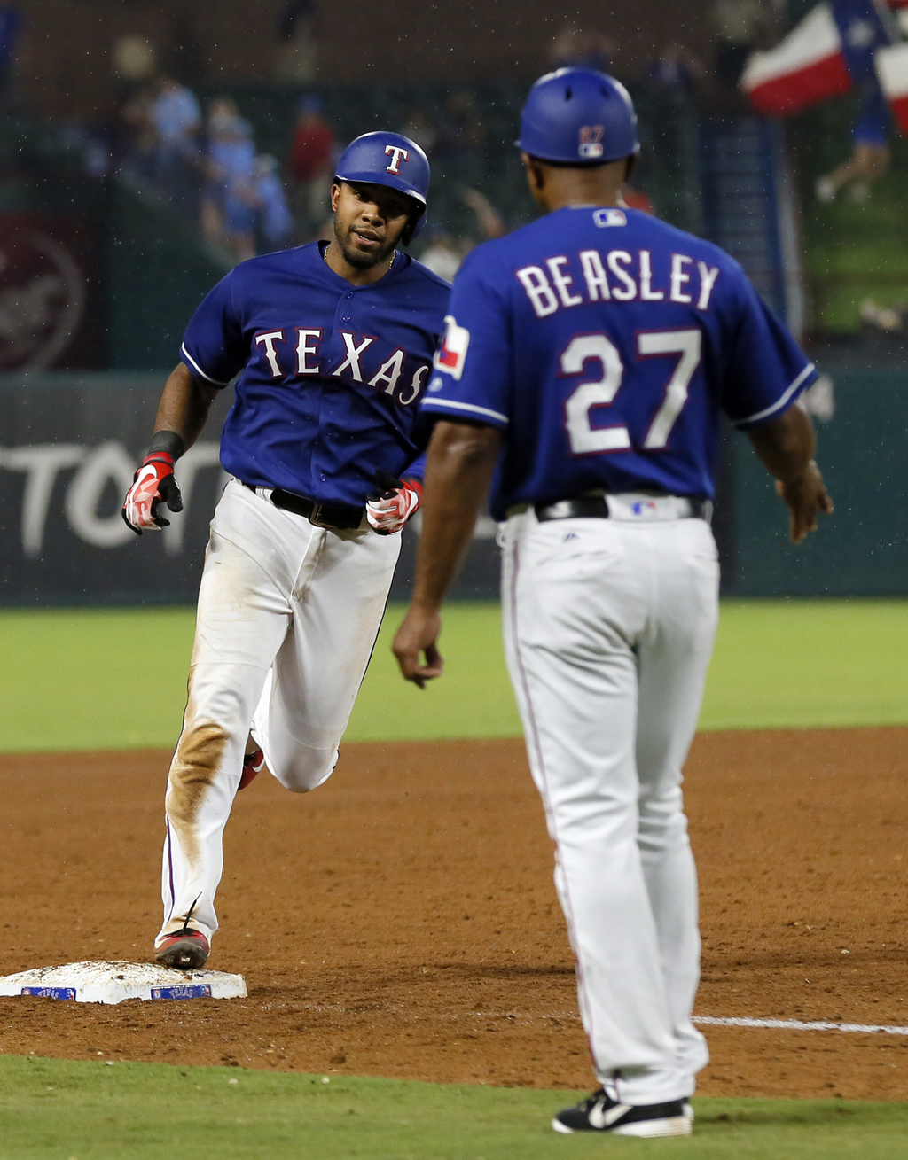 Texas Rangers' Elvis Andrus, left, rounds third past third base coach Tony Beasley (27) after hitting a two-run home run during the sixth inning of a ...