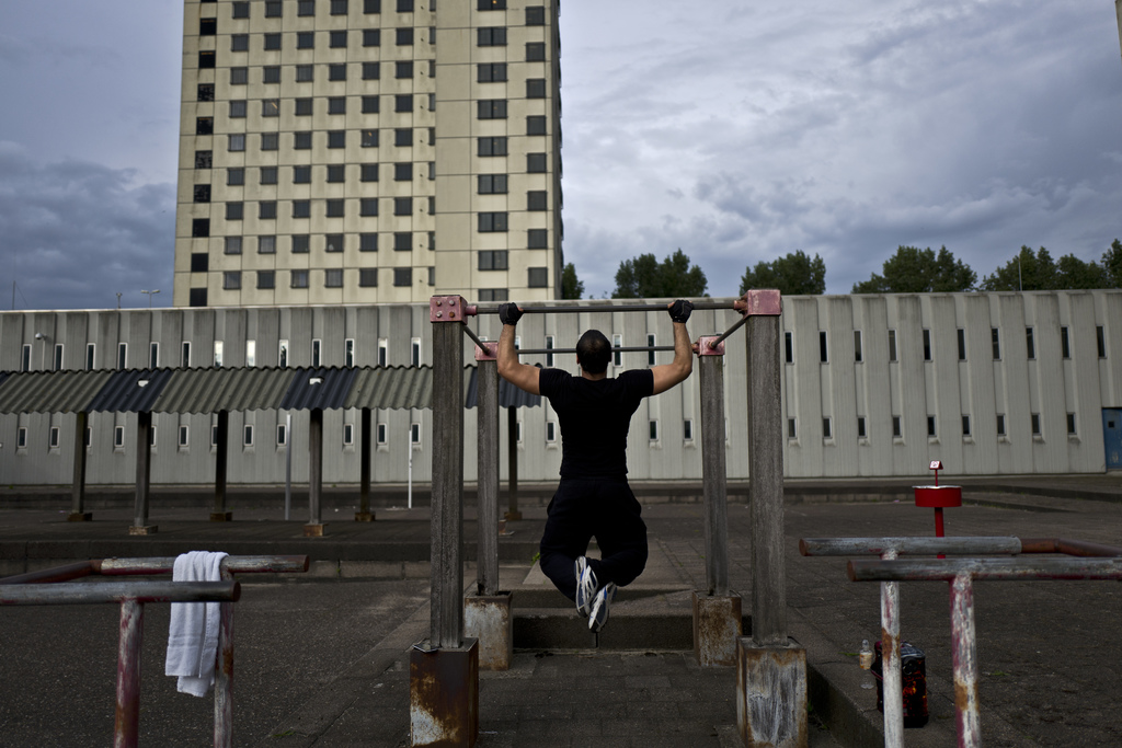 In this Saturday, July 22, 2017 photo, Afghan refugee Zafar Sahil, 22, exercises in a yard at the former prison of Bijlmerbajes in Amsterdam, Netherla...