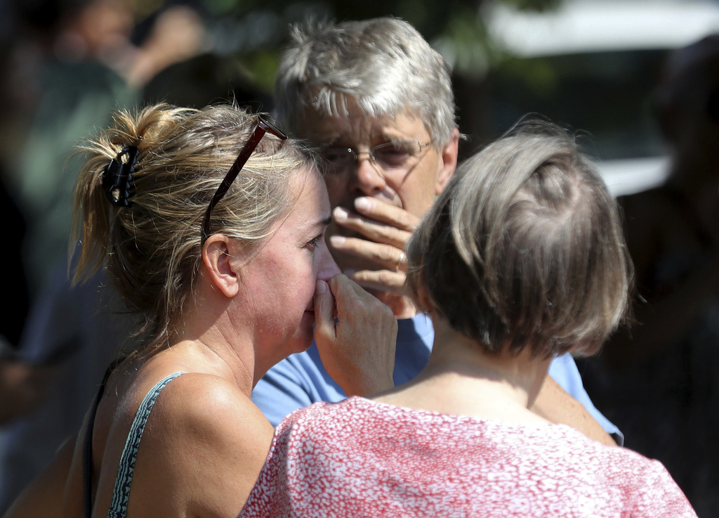 Former Minnehaha Academy employees Elizabeth Van Pilsum, left, and Rick Olson, center, react after an explosion at the school Wednesday, Aug. 2, 2017,...