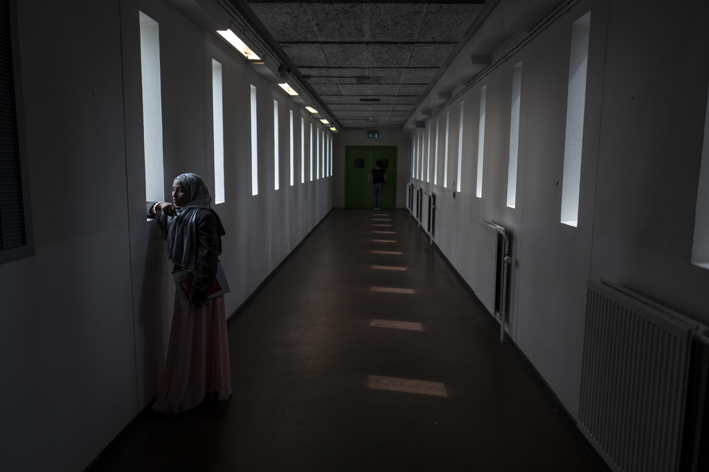 In this Thursday, July 13, 2017 photo, Ethiopian migrant Mako Husa, 40, looks out from a window of a corridor at the former prison of Bijlmerbajes in ...