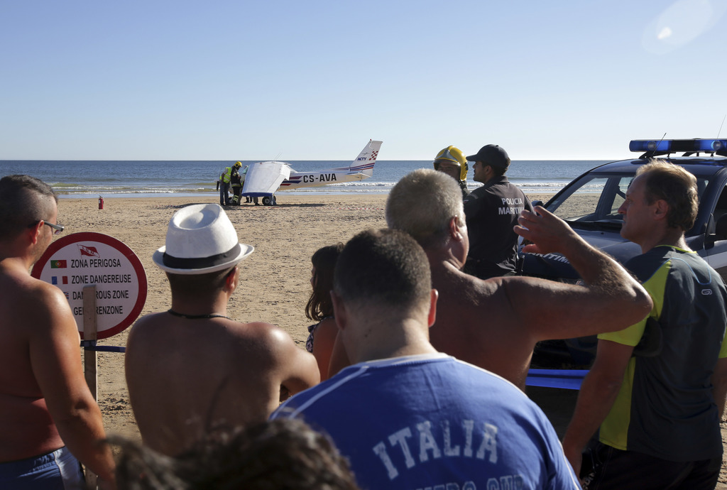 People look across at a small plane after an emergency landing on Sao Joao beach in Costa da Caparica, outside Lisbon, Wednesday, Aug. 2, 2017. The li...
