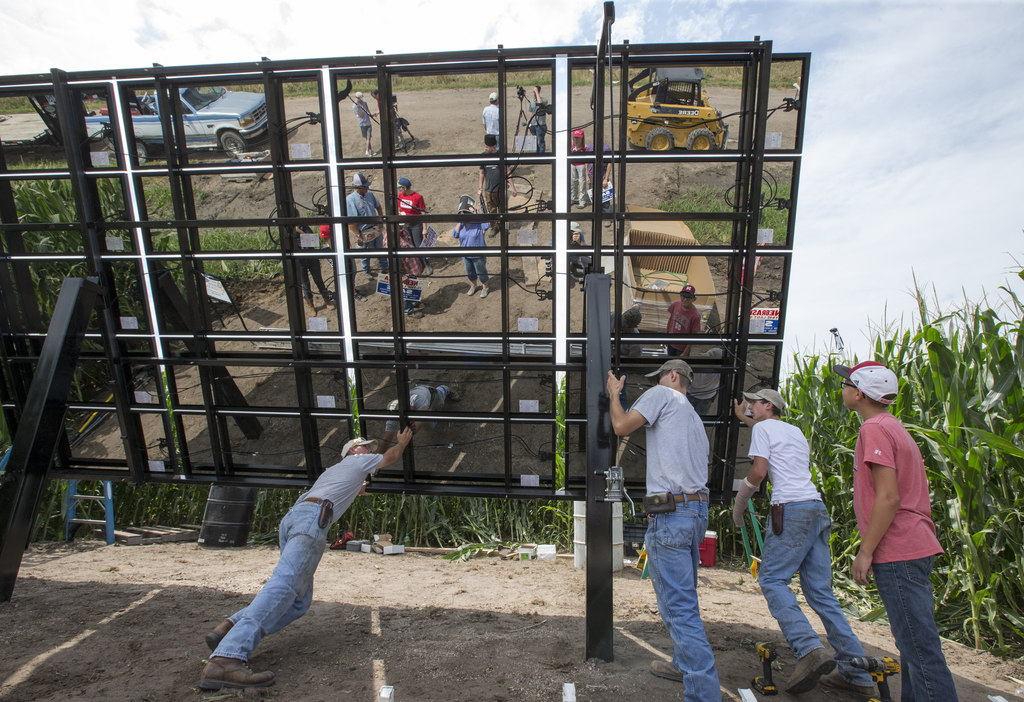 In this July 29, 2017 photo, volunteers and installers push into place an array of solar panels on the land of corn farmer Jim Carlson of Silver Creek...