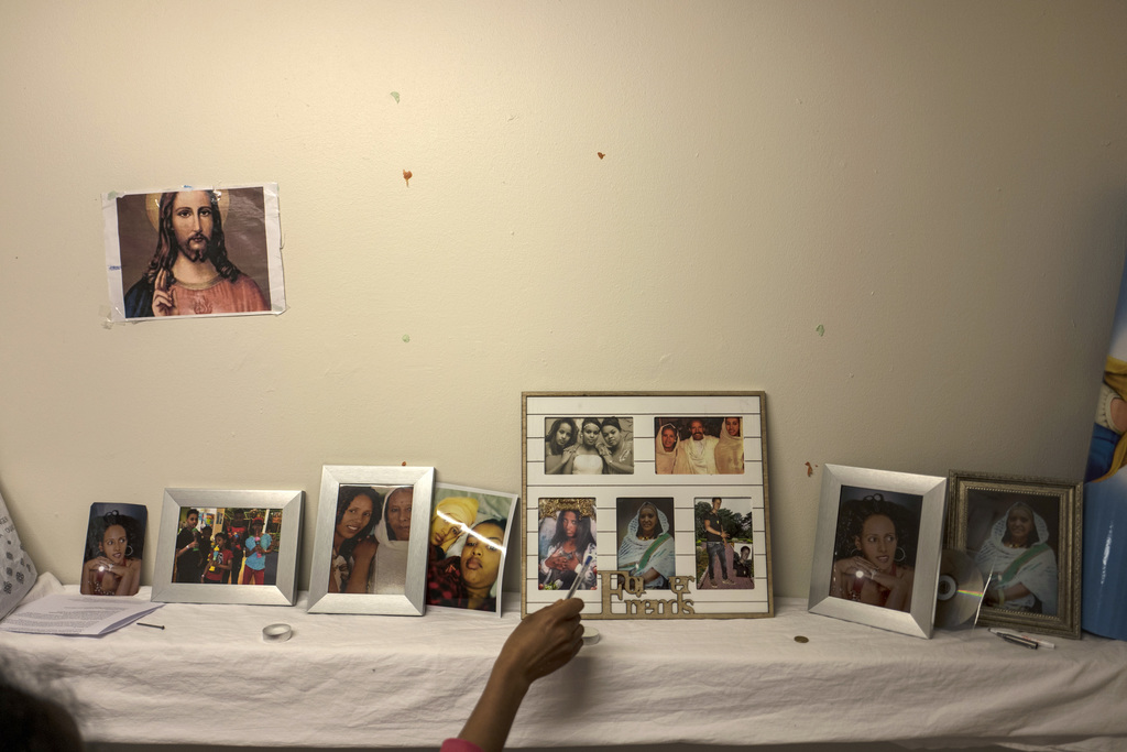 In this Sunday, July 9, 2017 photo, Eritrean migrant Ksanet Goitom, 23, points at pictures that she brought with her from Eritrea showing family membe...