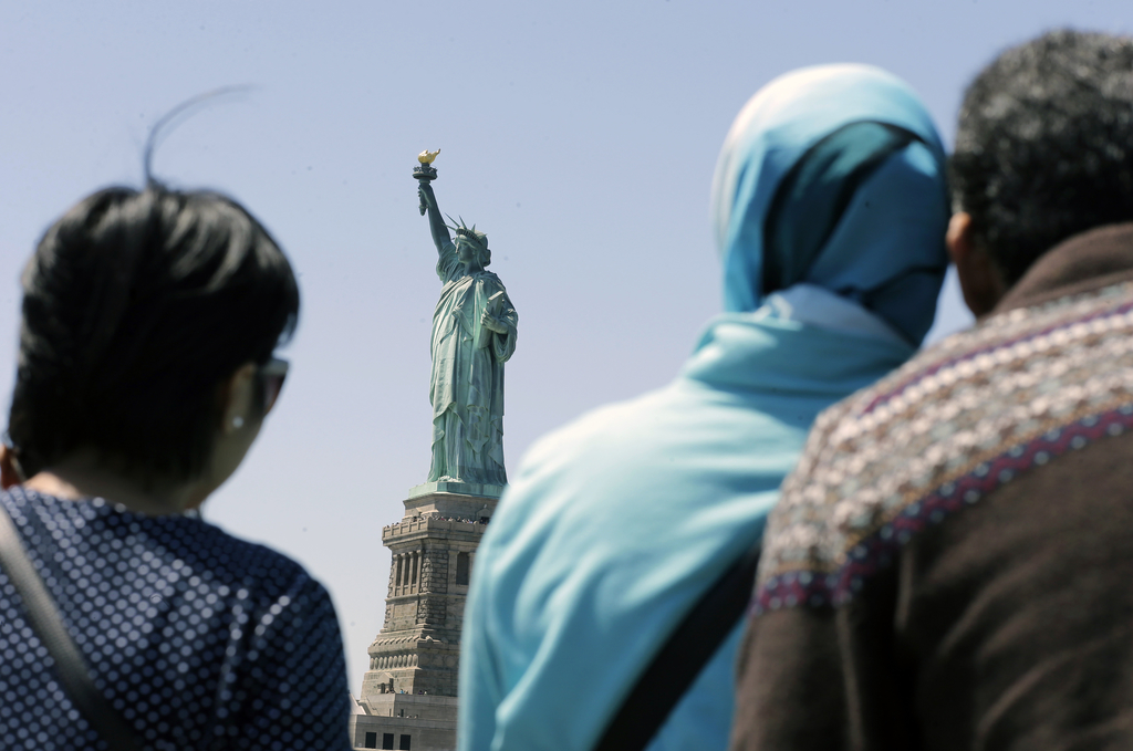 FILE - In this May 7, 2015, file photo, people look at the Statue of Liberty from a ferry boat in Jersey City, N.J. Senior White House aide Stephen Mi...