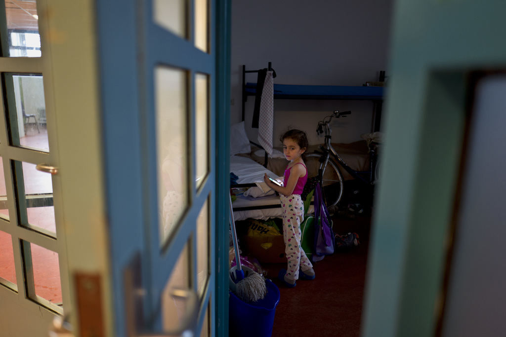 In this Friday, June 30, 2017 photo, refugee Sandi Yazji, 5, from al-Hasaka, Syria, holds a mobile phone while standing inside her room at the former ...