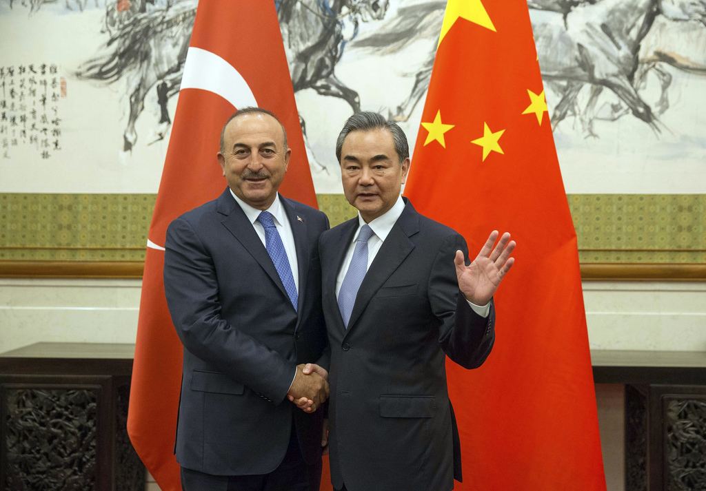 Chinese Foreign Minister Wang Yi, right, shakes hands with Turkish Foreign Minister Mevlut Cavusoglu during their meeting at Diaoyutai State Guesthous...