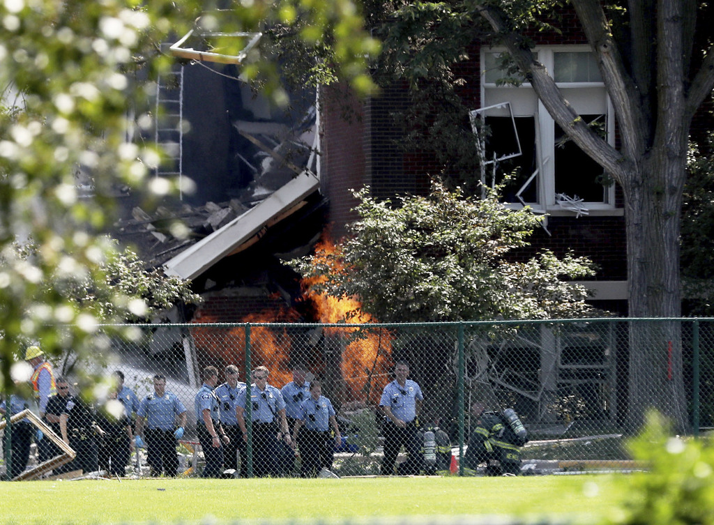 Emergency personnel move away as a gas fire continues to burn following an explosion at Minnehaha Academy Wednesday, Aug. 2, 2017, in Minneapolis. Sev...