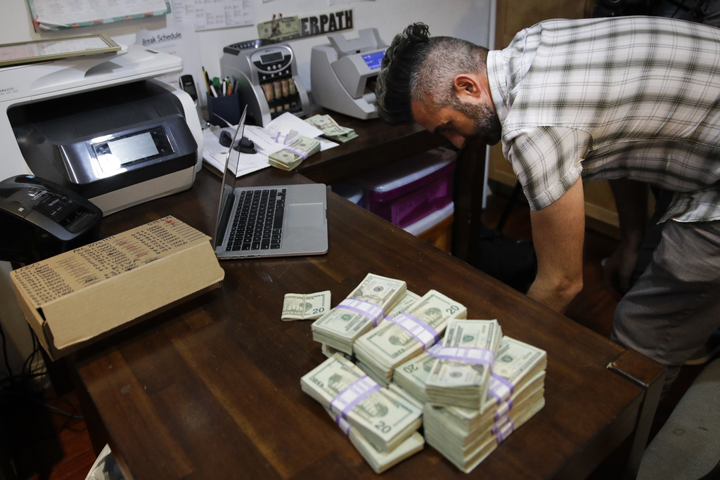 In this June 27, 2017, photo, bundles of $20 bills are placed on a table as Jerred Kiloh, owner of the Higher Path medical marijuana dispensary, prepa...