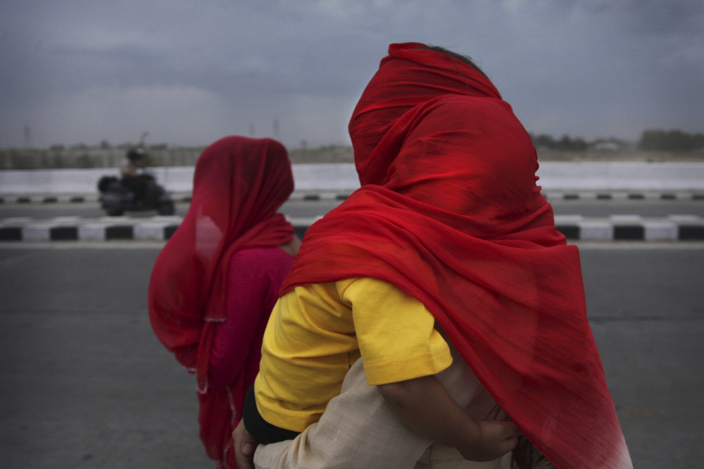 FILE - In this May 13, 2016, file photo, Indian women cover themselves and their children with scarves as they brave a dust storm under heat wave cond...