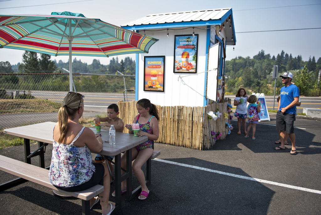 Families eat shaved ice at Tropical Sno, a seasonal spot in Vancouver, Wash., Wednesday, Aug. 2, 2017. Forecasts for triple-digit heat have caused a m...