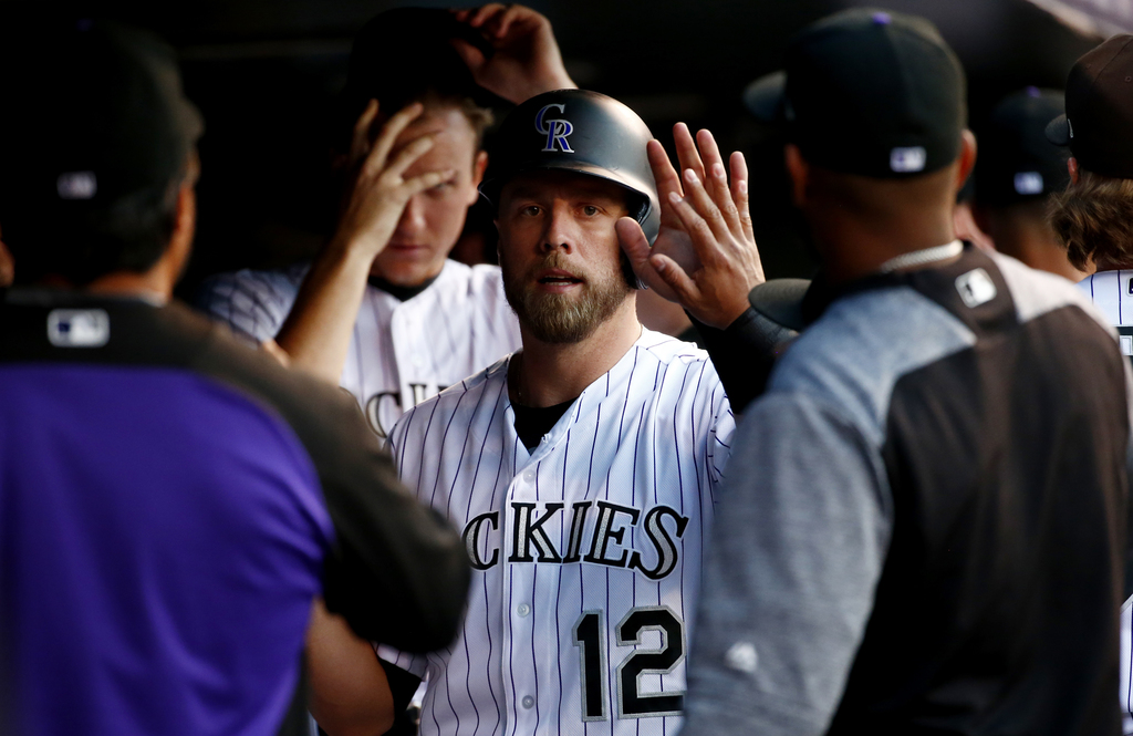 Colorado Rockies' Mark Reynolds is congratulated by teammates in the dugout after scoring on a Gerardo Parra two RBI double against the New York Mets ...