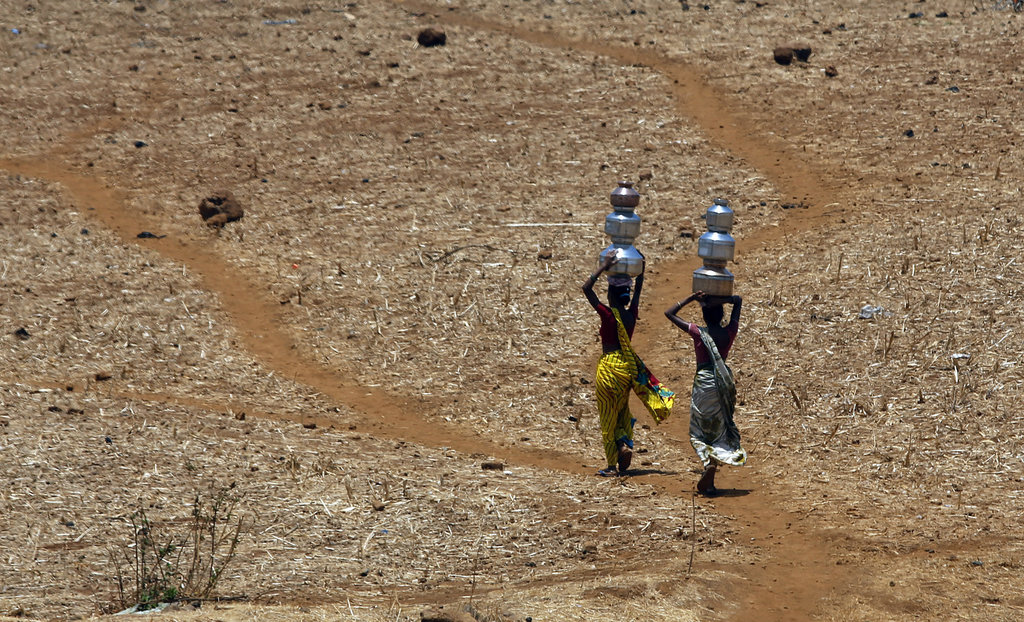 FILE- In this May 4, 2016 file photo, Indian women walk home after collecting drinking water from a well at Mengal Pada in Thane district in Maharasht...