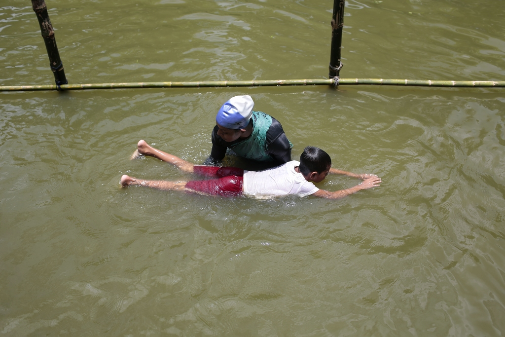 In this July 14, 2017 photo, a trainer helps a child to swim during a swimming training session at a pond in the Shishu Polli Plus area in Sreepur vil...