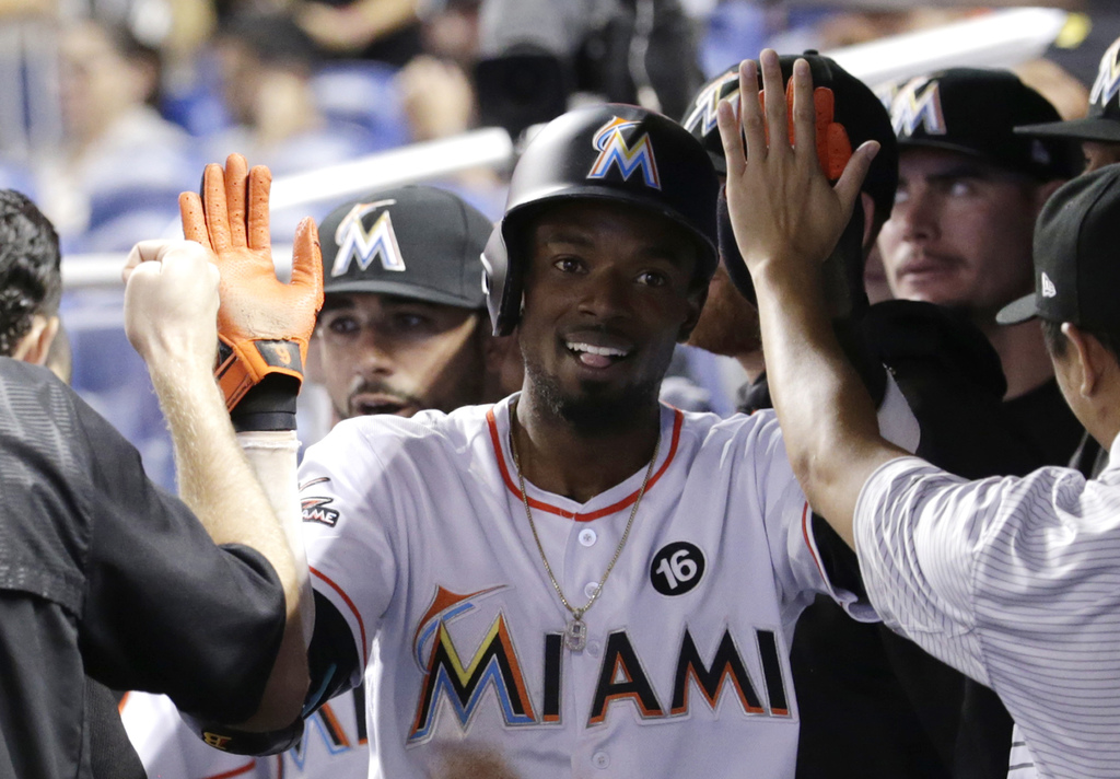 Miami Marlins' Dee Gordon is congratulated in the dugout after scoring on a double by Giancarlo Stanton during the first inning of the team's baseball...