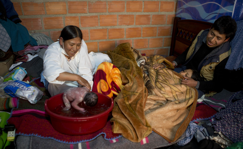 In this June 6, 2017 photo, midwife Ana Choque bathes newborn Abraham Dilan as his parents Mariana Limachi and Wilder Chambi rest on their bed after g...