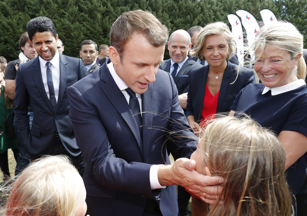 French President Emmanuel Macron greets while PSG President Nasser Al-Khelaifi, left, stands behind him as he attends at a charity holiday program eve...