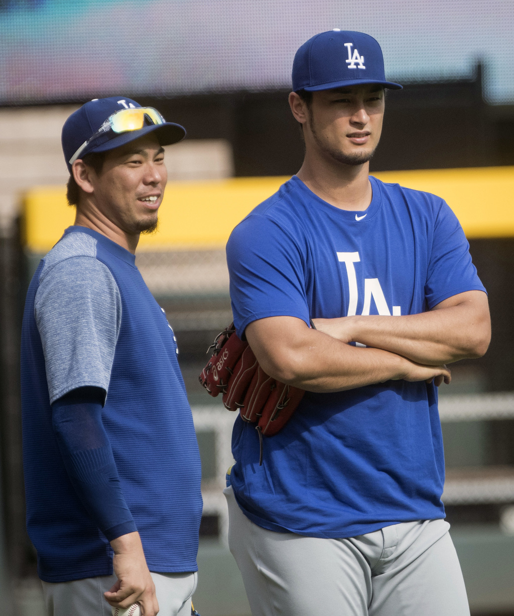 Los Angeles Dodgers pitchers Yu Darvish, right, and Kenta Maeda, both from Japan wait to warm up before a baseball game against the Atlanta Braves, We...
