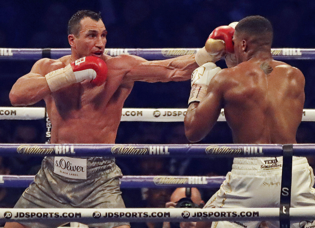 FILE - This is a  Saturday, April 29, 2017  file photo of Ukrainian boxer Wladimir Klitschko, left, as he lands a punch on British boxer Anthony Joshu...