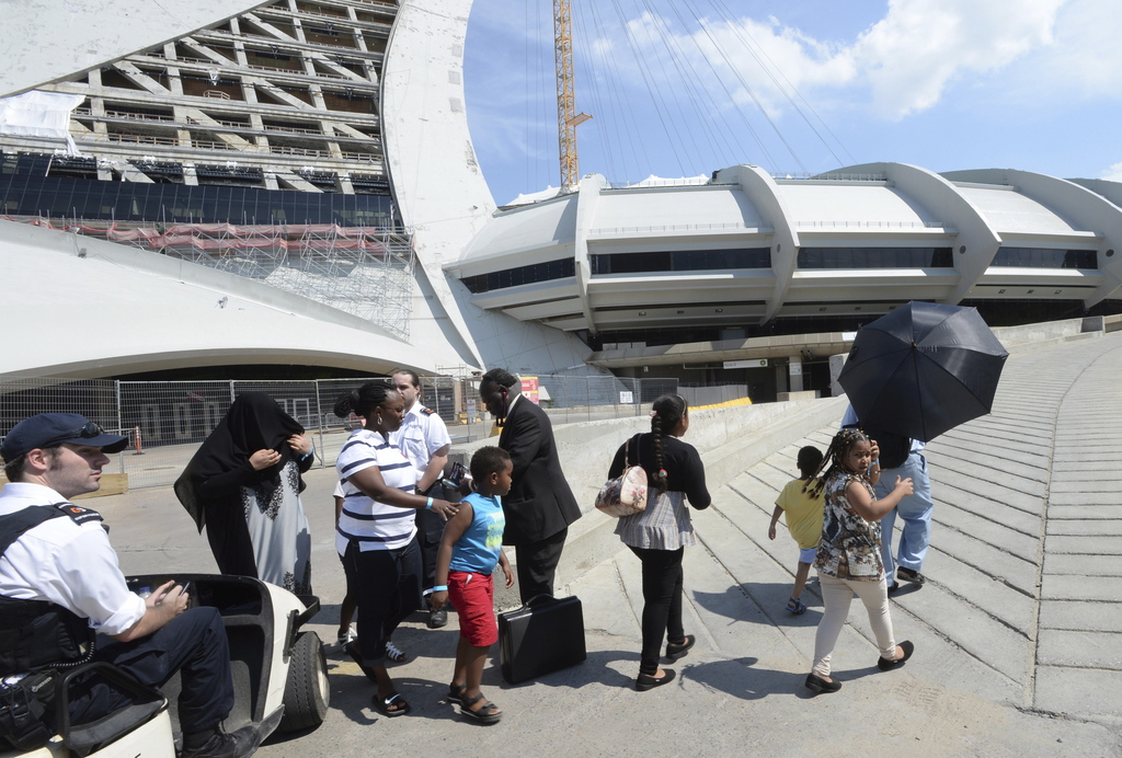 Asylum seekers take a walk outside Olympic Stadium as security guards look on in Montreal, Wednesday, Aug. 2, 2017. The stadium will be housing asylum...