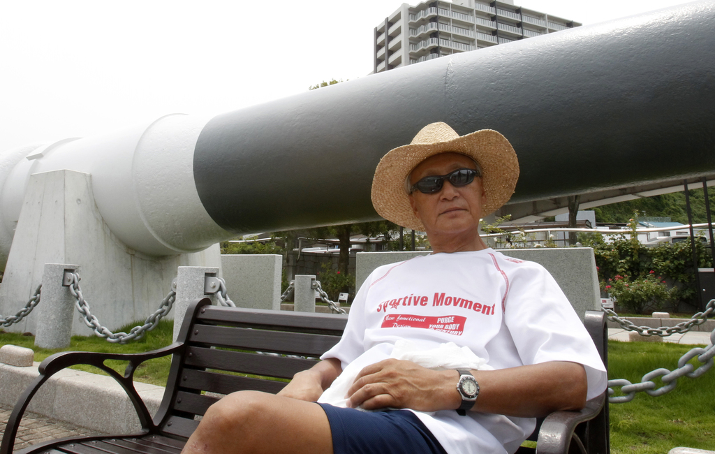 In this Tuesday, Aug. 1, 2017, photo, Akira Fukatsu, a 65-year-old retiree, sits in front of a replica cannon in Verny Park in Yokosuka, south of Toky...