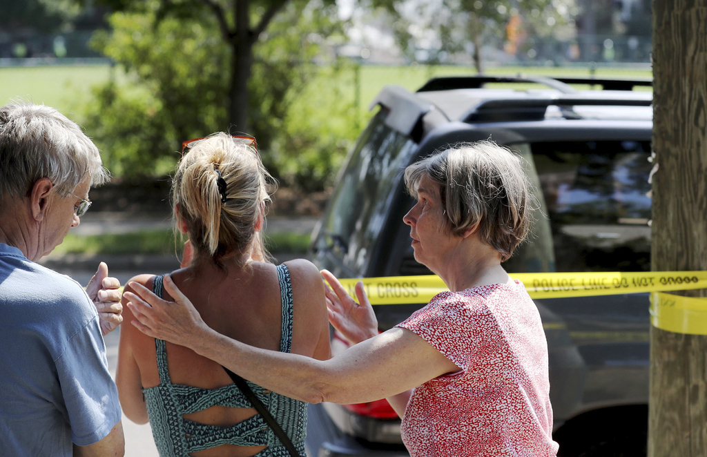 Former Minnehaha Academy employees Elizabeth Van Pilsum, center, is comforted by friends Edie Olson, right, and Rick Olson, left, after an explosion a...