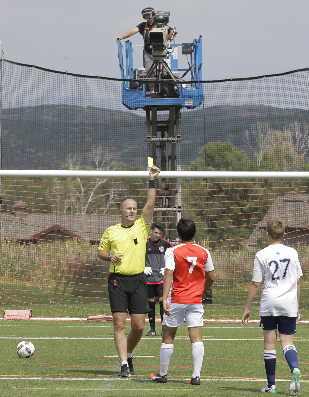 In this July 11, 2017, photo, MLS referee Silviu Petrescu raises a yellow card against a player after using video replay during scrimmages organized i...